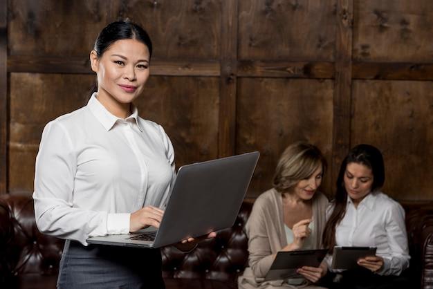 Donna di vista frontale con il computer portatile alla riunione
