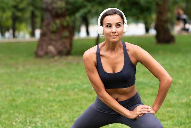 Donna di vista frontale con l'esercizio delle cuffie