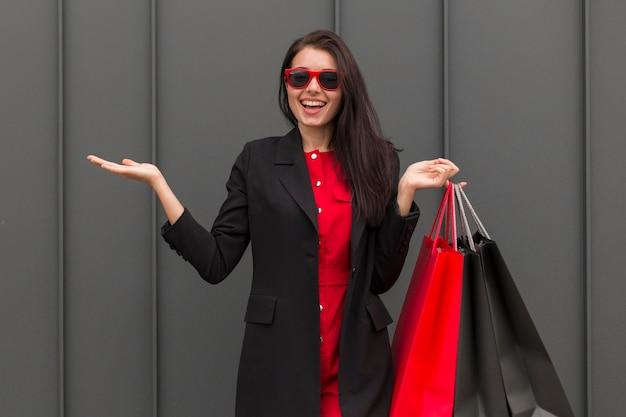 Donna di vista frontale di vendite venerdì nero con borse della spesa