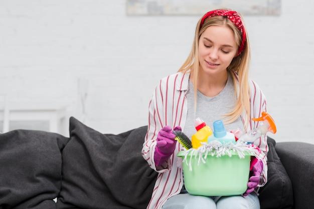 Donna di vista frontale sul divano con prodotti per la pulizia
