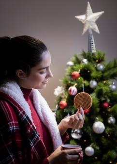 Donna di vista laterale che beve tè e che mangia biscotto