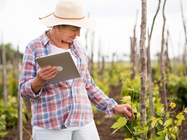 Donna di vista laterale che controlla il suo giardino