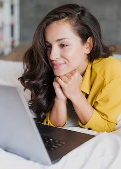 Donna di vista laterale che esamina computer portatile