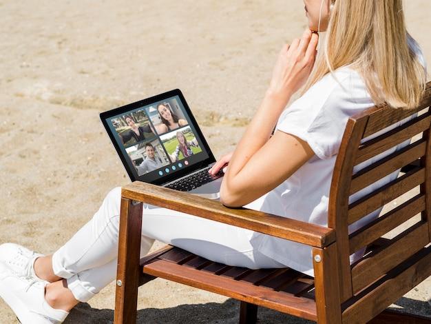 Donna di vista laterale che ha una videochiamata all'esterno