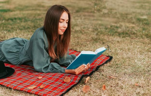 Donna di vista laterale che legge un libro su una coperta da picnic