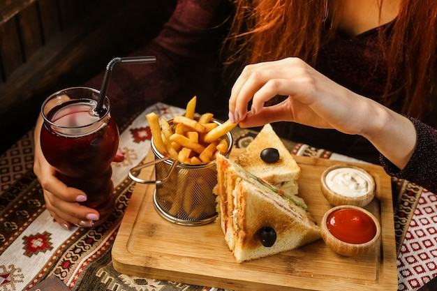Donna di vista laterale che mangia le patate fritte con ketchup e maionese del panino di club sul supporto con la bibita