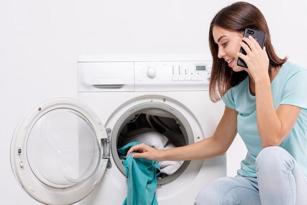 Donna di vista laterale che parla sul telefono nella stanza di lavanderia