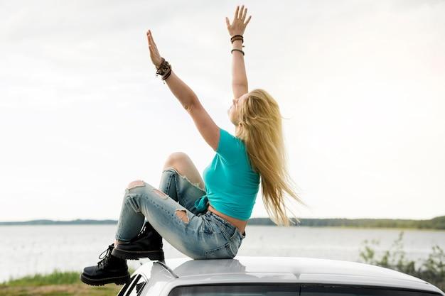 Donna di vista laterale che si siede sull'automobile