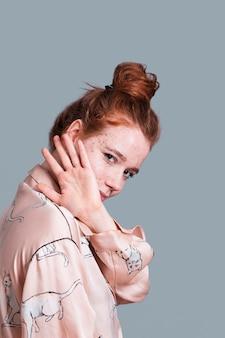 Donna di vista laterale con la posa del panino dei capelli