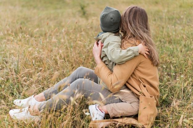 Donna di vista posteriore che abbraccia suo figlio
