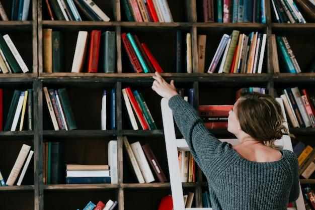 Donna di vista posteriore che sceglie libro dallo scaffale