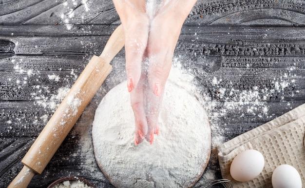 Donna di vista superiore che prepara dolce con il matterello, farina, uova sulla tavola su superficie di legno. orizzontale