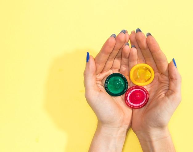 Donna di vista superiore che tiene tre preservativi