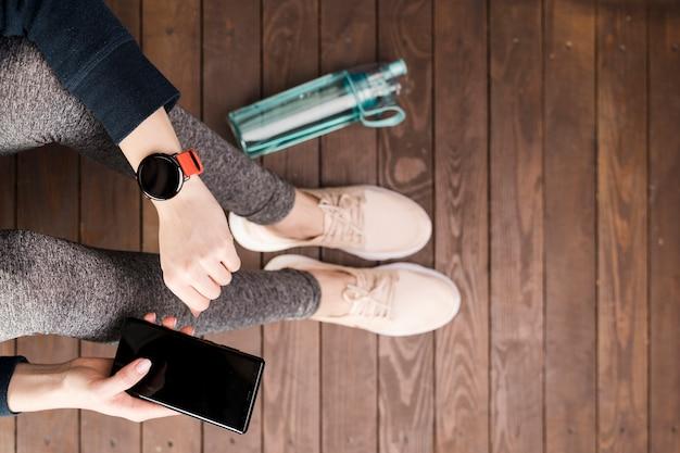 Donna di vista superiore in abbigliamento sportivo che tiene telefono cellulare