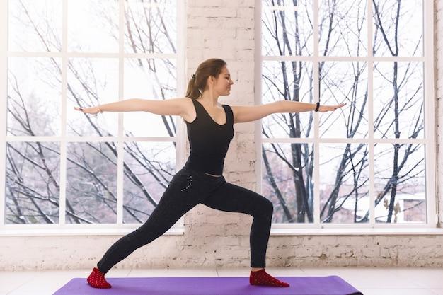Donna di yoga che fa posa diritta di virabhadrasana nella stanza leggera sopra