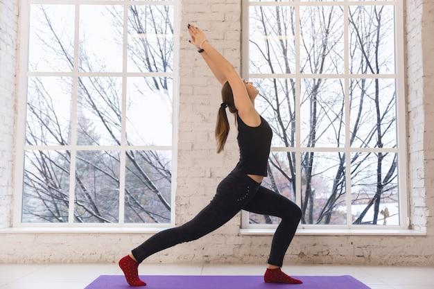 Donna di yoga che fa virabhadrasana