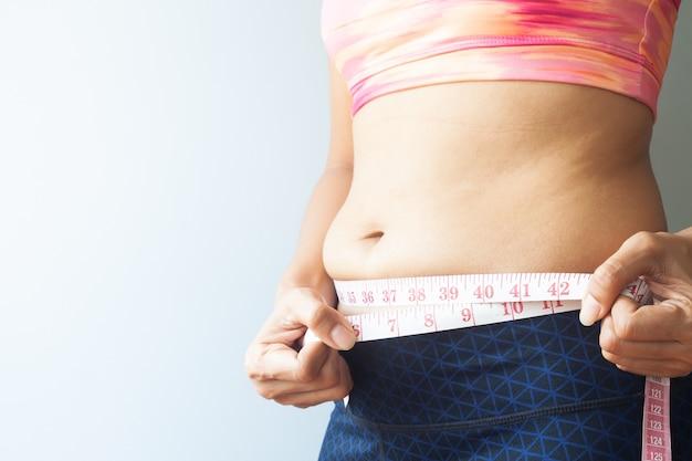 Donna dimagrante con grasso della pancia, donna sportiva che misura il grasso della pancia. avvicinamento