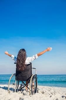 Donna disabile con le braccia tese in spiaggia