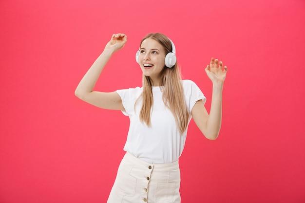 Donna divertente con le cuffie ballando cantando e ascoltando la musica