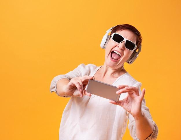 Donna divertente dei pantaloni a vita bassa che prende i selfie