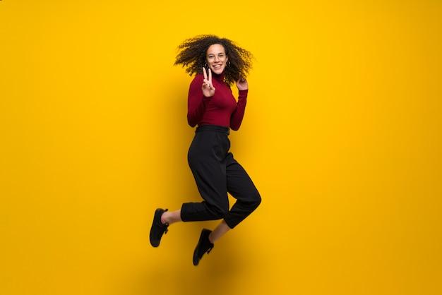 Donna domenicana con capelli ricci che salta sopra la parete gialla isolata