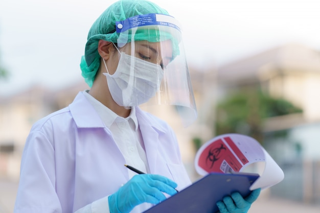 Donna dottoressa, con cartella per referti paziente, ritratto all'aperto, pandemia di coronavirus covid-19. (codice qr e codice a barre falsi)