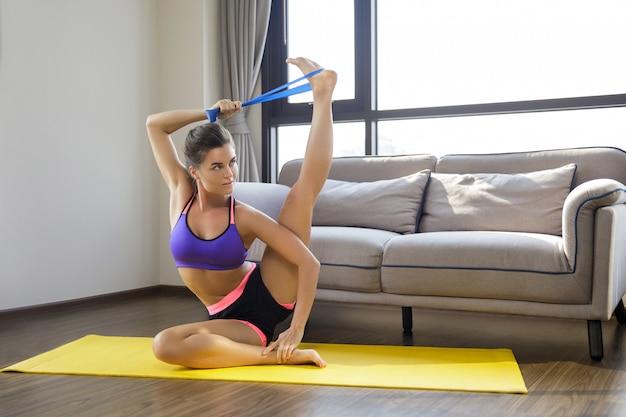 Donna durante l'allenamento a casa con ð ° elastico in gomma