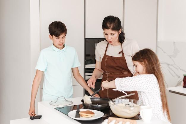 Donna e bambini felici 8-10 cucinare insieme e friggere frittelle sul fornello moderno in cucina a casa