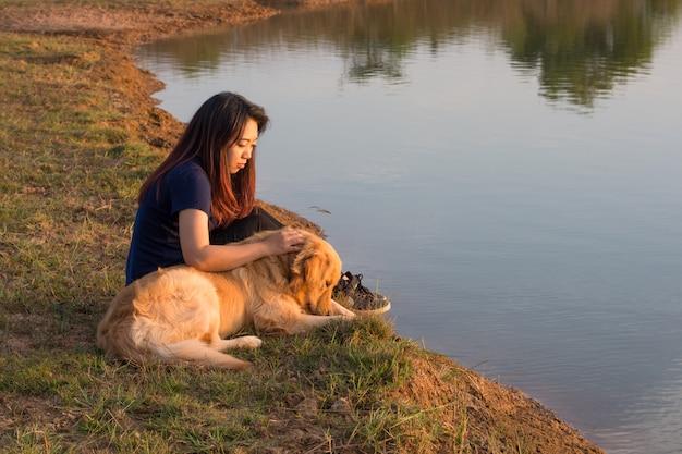 Donna e cane dorato sulla riva del fiume