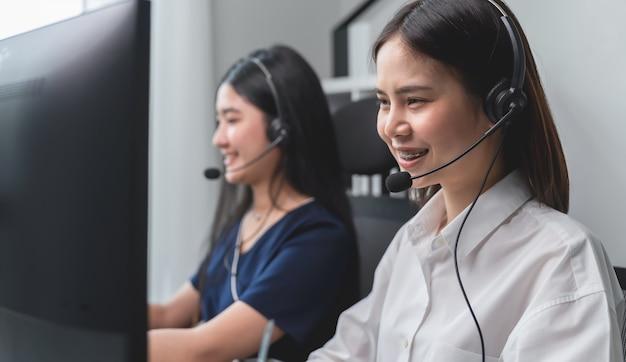Donna e gruppo di affari asiatici sorridenti che lavorano nella call center alla scrivania con la cuffia avricolare e il computer.