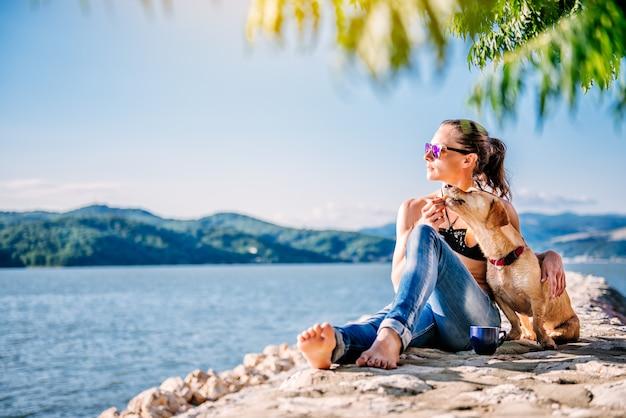 Donna e il suo cane godendo su una spiaggia e condividendo i biscotti