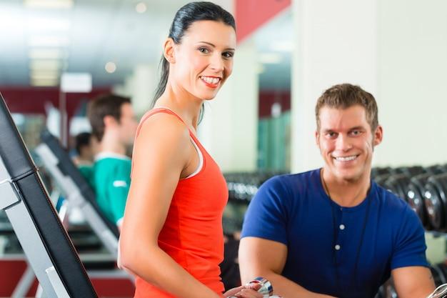 Donna e personal trainer in palestra con manubri