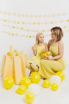 Donna e ragazza che posano mentre si tengono i limoni