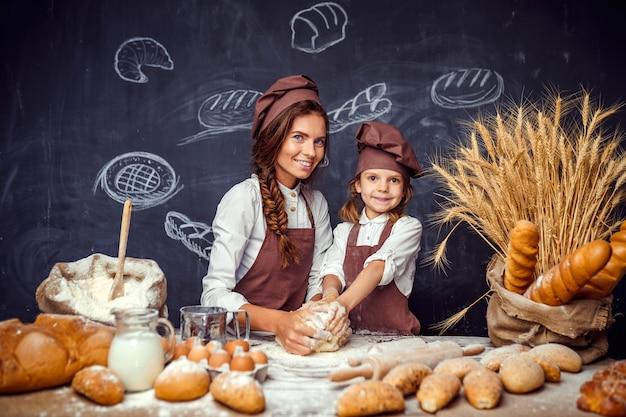 Donna e ragazza che producono insieme le pasticcerie