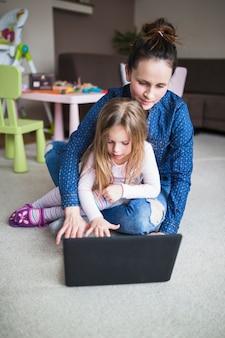Donna e sua figlia che si siedono sul tappeto facendo uso del computer portatile
