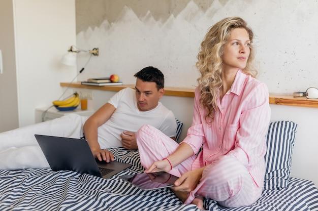 Donna e uomo a letto al mattino sorridendo felici lavorando online, famiglia che vive insieme in camera da letto indossando pigiami