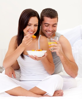 Donna e uomo che mangiano prima colazione nutriente a letto