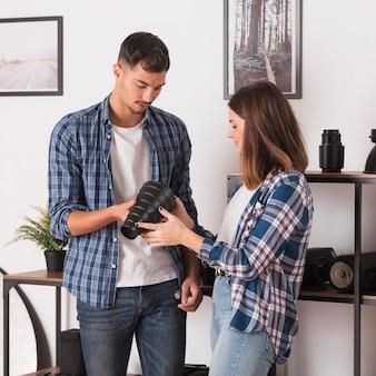 Donna e uomo che scelgono la loro attrezzatura per un servizio fotografico