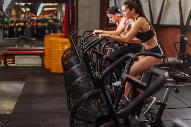 Donna e uomo in bicicletta in palestra, esercitando le gambe facendo bici allenamento ciclismo cardio