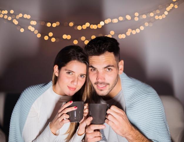 Donna e uomo in coverlet con tazze sul divano in camera oscura