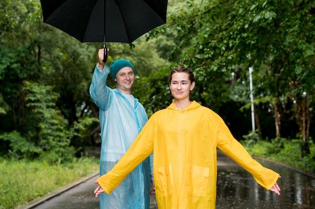 Donna e uomo in posa sotto la pioggia