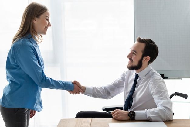 Donna e uomo positivi che stringono insieme le mani