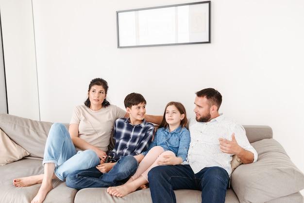 Donna e uomo seduto sul divano insieme, con bambini ragazza e ragazzo nel soggiorno di casa