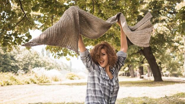 Donna eccitata con sciarpa nel parco