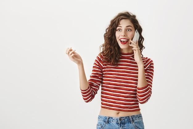 Donna eccitata sorpresa che parla sul telefono cellulare, sorridendo stupita