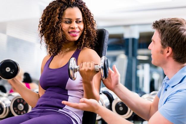 Donna ed istruttore africani all'esercizio in palestra