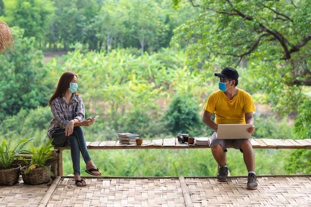 Donna ed uomo asiatici nell'allontanamento sociale che si siede sul banco in mezzo alla natura, concetto di allontanamento sociale.
