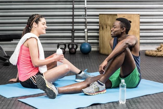 Donna ed uomo che parlano sull'asciugamano di sport alla palestra del crossfit