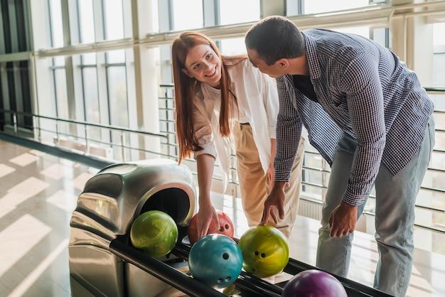 Donna ed uomo che prendono le palle da bowling variopinte