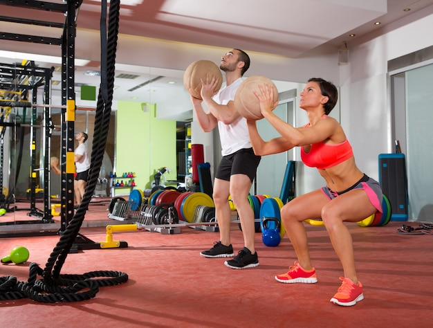 Donna ed uomo del gruppo di allenamento di forma fisica della palla di crossfit